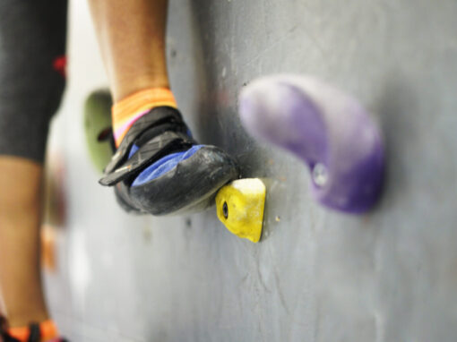 Climbing rocks on climbing wall. Fitness, extreme sport, bouldering, people and healthy lifestyle concept - people exercising at indoor climbing gym. Close-up image